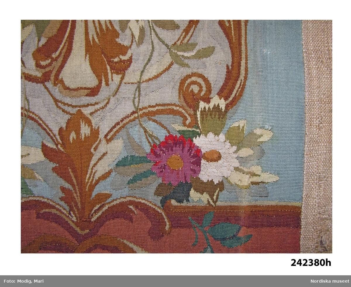 """Huvudliggaren: """"a-i Tapeter, till helt rum, i haute-lisse, ylle på llinvarp, blågrön botten med gråvita fält och blommor i färger; lister i brunt. 4 väggfält: 365 x 140 cm.; 1 dito; 365 x 106 cm.; 2 pilastrar; 365 x 33,5 cm.; 2 dörröverstycken: 48 x 74 cm."""""""