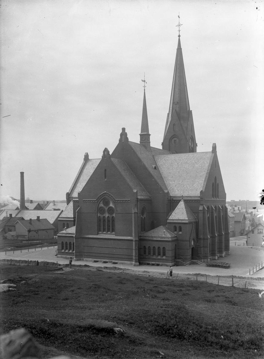 Vår Frelsers kirke en vinterdag sett fra øst. To personer står bak kirken.  Trehusbebyggelse på begge sider av kirken.