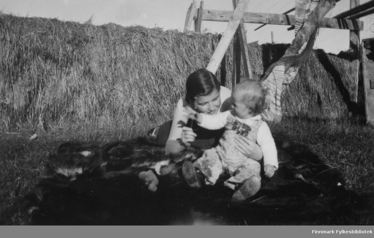 Solveig Evanger leker med Pia Gunnari på et dyreskinn, sommeren 1935. I bakgrunnen fulle høyhesjer.