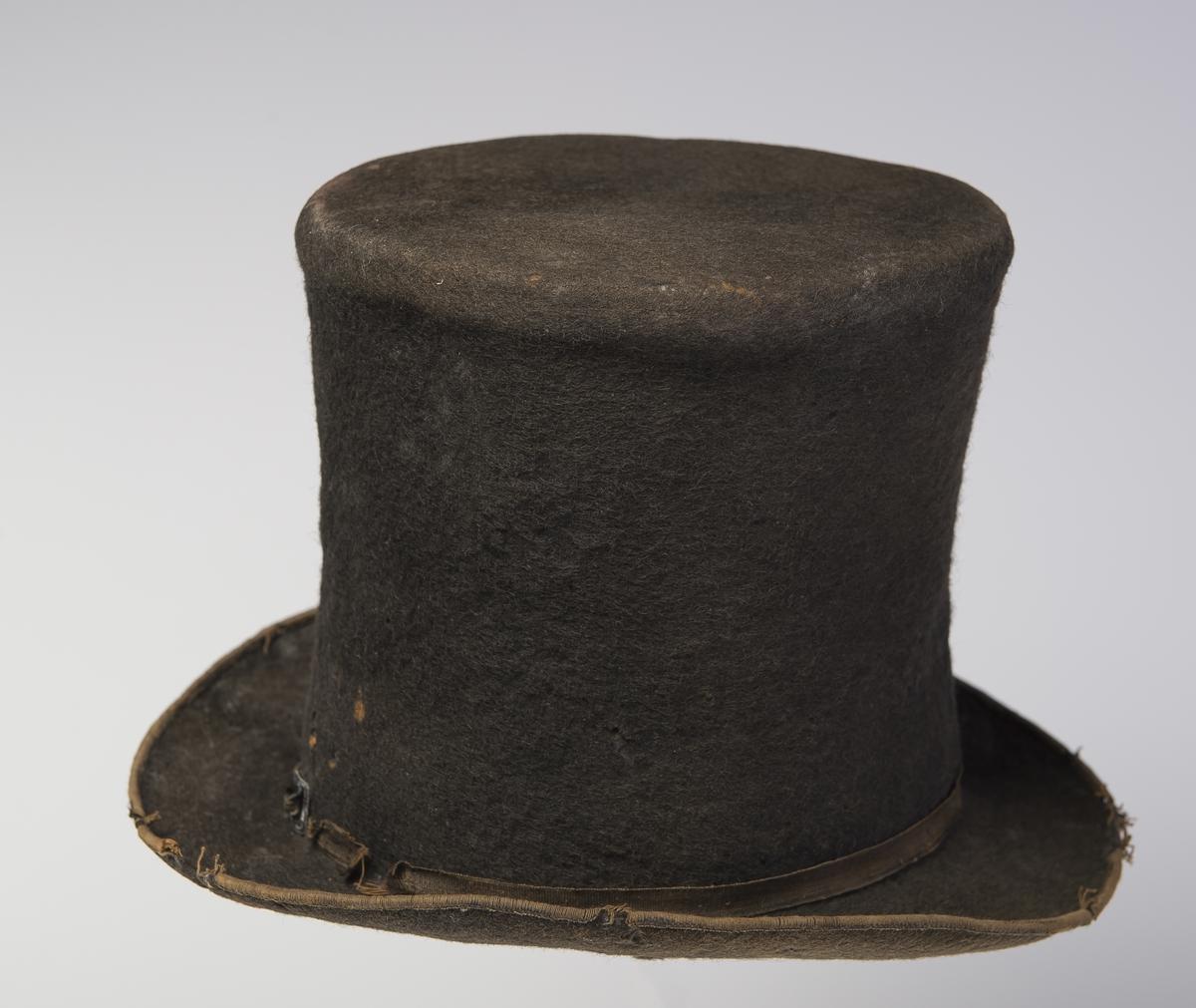 Filthatt med høy stiv pull som er flat på toppen. Rundt ytterkanten av bremmen er det påsydd et smalt bånd. Rundt nedre kant av pullen er det er smalt dekorbånd med liten spenne. Inne i pullen er det et papir med trykk på. Hatten har svettebånd og halve høyden av hatten er foret. Øvre del av hatten har større omkrets enn lenger nede. Denne type hatt er forløperen til flosshatt.