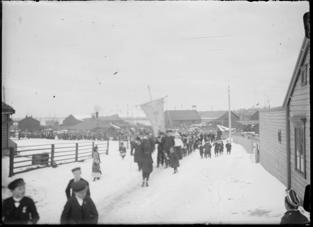 Vi antar at dette er 1.mai-toget i Vardø, fotografert en gang mellom 1910-1920 av sognepresten Johan Oskar Andreas Grasmo. I front ser man gutter med sjakettlue og dress med medaljer. Bak dem kommer toget med fane i front. Toget er langt og strekker seg flere hundre meter nedover veien. Det er fortsatt mye snø i Vardø. Bak i bildet, helt til venstre mellom to hus skimter man et større skip med flere master som ligger forankret i havna.