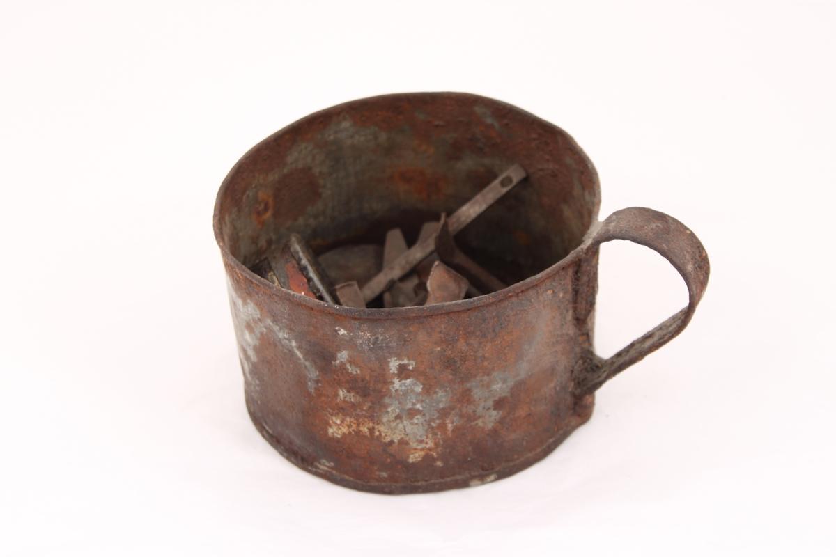 En metallkopp med ulike gjenstander.  Koppen inneholder; en beltespenne, to runde metallbokser, tre pinsetter, diverse nøkler(?), tråd til beksøm(?) og skruer i ulik størrelse.