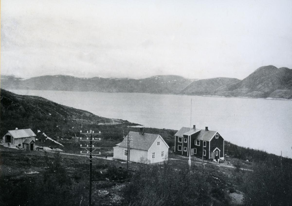 Oversiktbilde av bygninger på skiferbruddet i Friarfjord. Bygningen helt til venstre er fjøset. Den lyse bygningen til høyre ble trolig brukt som post- og kontorbygg. Den mørkere bygningen nærmest havet er brakkene til de som arbeidet på bruddet. I bakgrunnen kan man se havet og fjell. I forgrunnen ser man strømlinjer som fører til bygningene.
