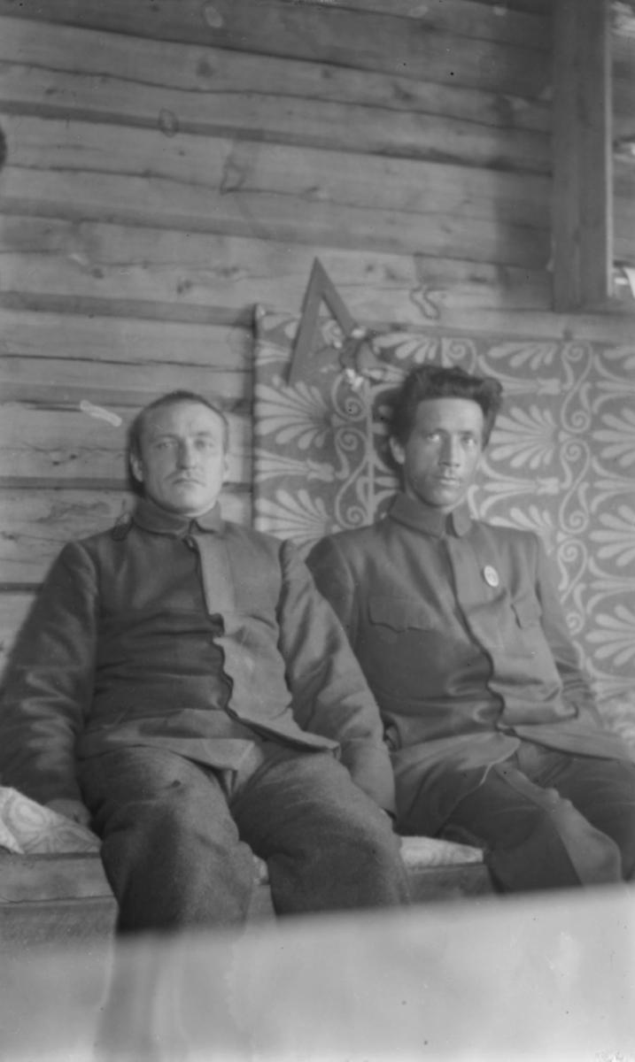 To menn sittende inne ved en tømmervegg - de er kledd i uniformer. Dette kan ære interiør fra en kaserne, jfr. bildets påskrift. Bak mennenes rygg et tekstil i vakkert liljemønster