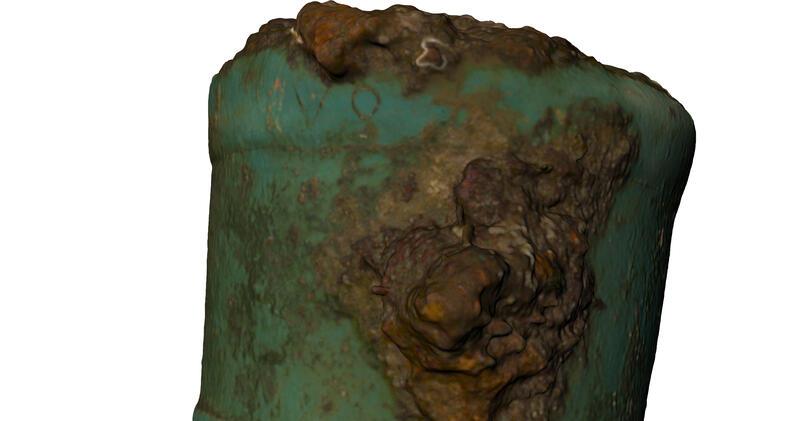 """Bakre ende av kanon. Metallet er grønt etter å ha ligget i sjøen i lang tid, stedvis er det også brun-oransje rustklumper. En """"V"""" og en """"o"""" er risset inn på bakstykket av kanonen. Noe bortenfor dette er også noe som kan være et innrisset kors, delvis dekt av korrosjon. (Foto/Photo)"""