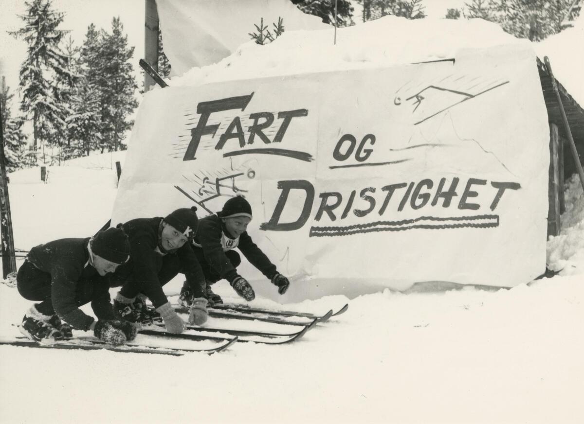 Skiløpere foran skilt. (Foto/Photo)