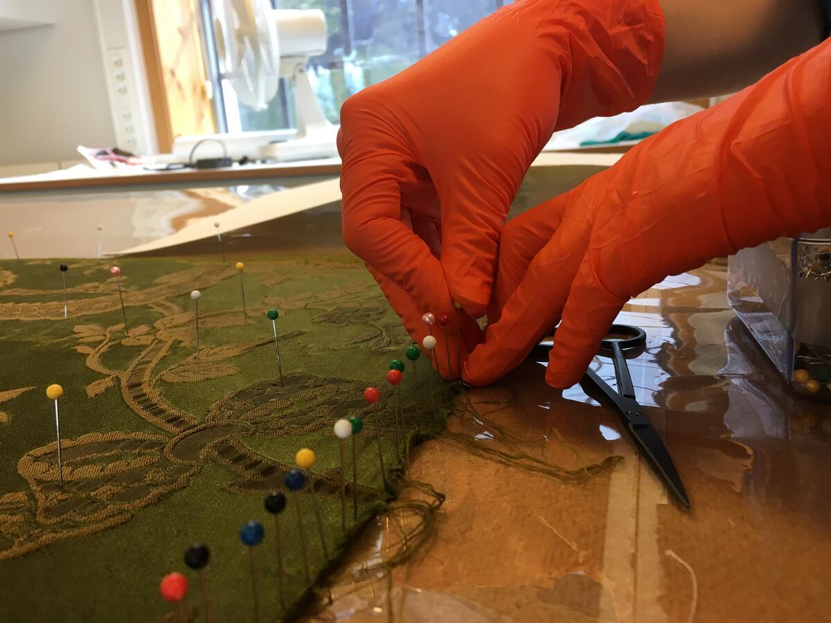 Ein tekstil blir spent opp med nåler, for tørking (Foto/Photo)