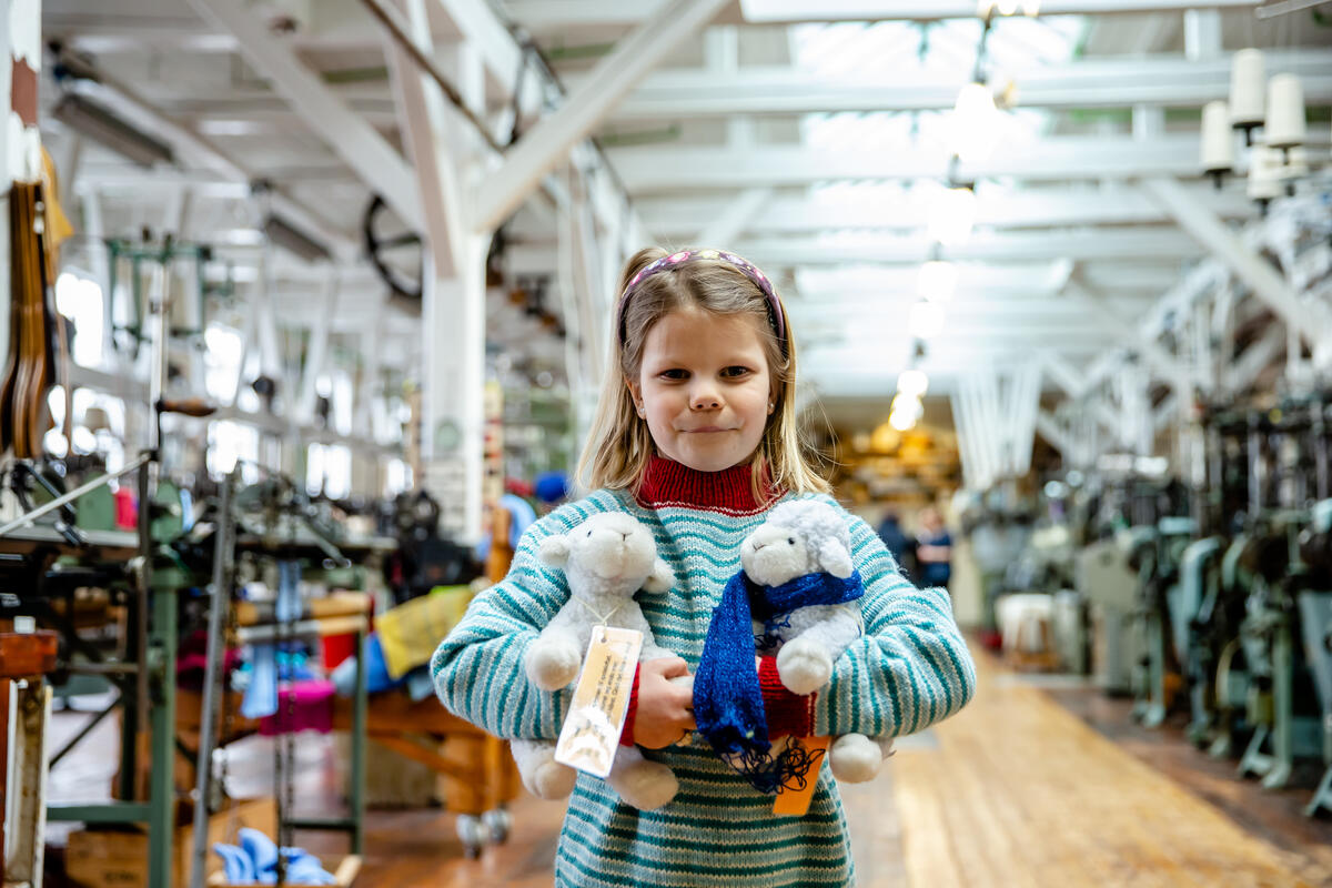 jente med kosedyr i fabrikklokale (Foto/Photo)