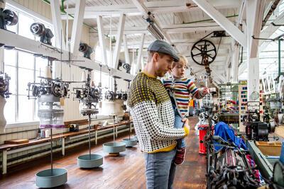 mann og barn i fabrikklokale med maskiner. Foto/Photo