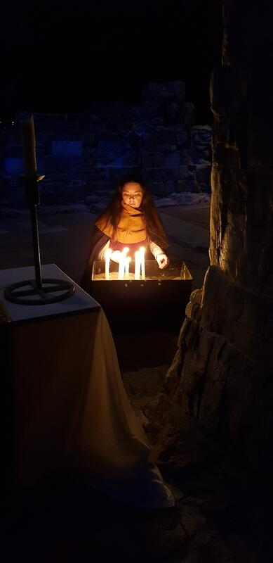 En middelalderkledd ung kvinne tenner levende lys under ruinbuene i Hamardomen. (Foto/Photo)