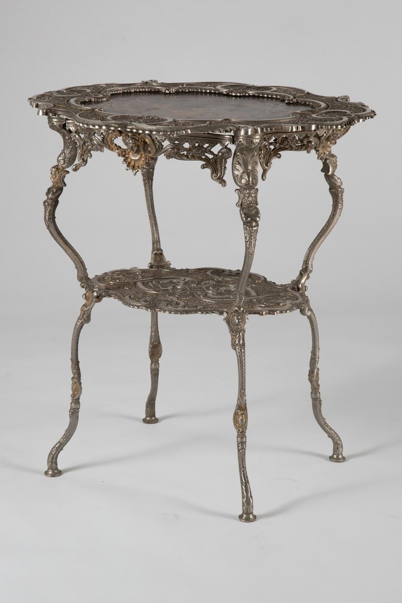 """Forsølvet, ovalt støpjernsbord (gueridon) i to etasjer med sterkt profilert ramme omkring en innfelt treplate øverst. På platen er trykt et Fêtes galante-maleri, dvs. en kjærlighetsscene i en park, her innskrevet i en rokokkolignende kartusj, og senere overlakkert.  Omfattende, støpt nyrokokko-dekor, med bølgende C-former, skjell og palmettlignende motiver. I tillegg 4 ornamentale figurfelt på øvre plate med putti, samt kvinnehoder på sargen og mannshoder på benas knær.  En mindre støpejernsplate nede, mellom de 4, svært tynne bena. Sargen er gjennombrutt, og både den og resten av bordet er satt sammen av mange separate, prefabrikerte støpejernsdeler. Alle deler er skrudd sammen, med til dels store, """"moderne"""" skruer. Hver støpte del er påført støpt fabrikkmerke og nummer."""
