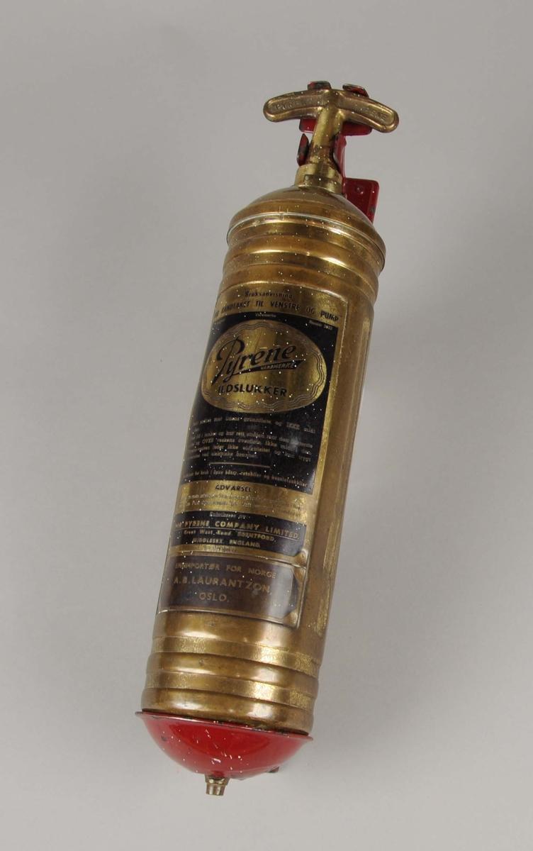 Brannslukkningsapparat med veggfeste. Apparatet er sylinderformet med konveks bunn og pumpehåndtak øverst. På apparatet er det festet en bruksanvisning, en rektangulær metalletikett.