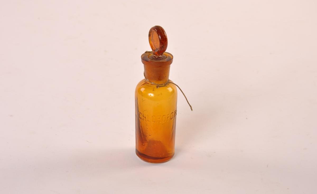 Sylindriske apotekerflasker i brunt glass. Glasspropp med rundt hode