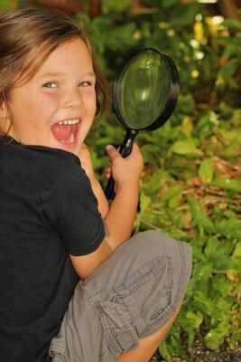 Bildet viser ei jente med forstørrelsesglass. Foto/Photo
