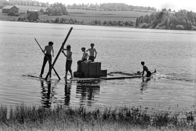 Svart-hvitt bilde av fem ungdommer i shorts som seiler på en hjemmelaget flåte.. Foto/Photo