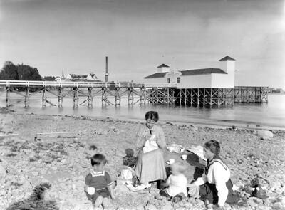 Svart-hvitt foto av to kvinner og to barn som sitter på en steinete strand ved Mjøsa. Hamar badehus i bakgrunnen.. Foto/Photo