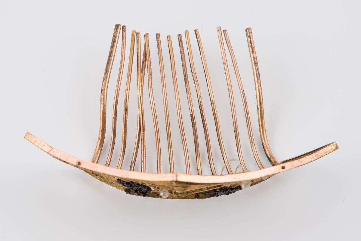 Oppstående, 5-kantet front, med utskrådde sider og opp i spiss midt foran. Ytre ramme og 14 lange tenner av kobber, innvendig fylt med gjennombrutt og siselert motiv i forgylt messing. Midt foran en stor, naturalistisk rose med blader, innskrevet i en skjoldformet ramme av tettstilte ringer, symmetrisk flankert av gjennombrutt felt med vinløv med en drueranke av ørsmå, svarte glassperler. Motivet, især drueklasene, er 3-dimensjonalt i sin utforming. Skjoldformens åpne ringer var antagelig opprinnelig fylt av hver sin, litt større glassperle. Nå er det kun 3 igjen, festet med gul tråd. Tennene på kammen er lange, festet til forstykkets nedre kant og bøyd oppover og bakover i en bue.