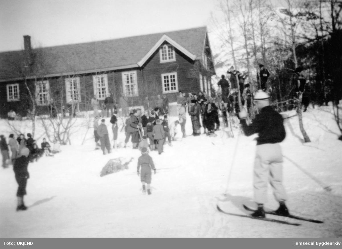 """Kretsrenn på nedsida av """"gamle"""" Hugnadheim i 1946. Me ser:  Iver T. Svare, tidtagersjef. Bak Iver T. står Ola N. Hulbak. Skiløper i framgrunnen er Jens Sletto frå Hol"""
