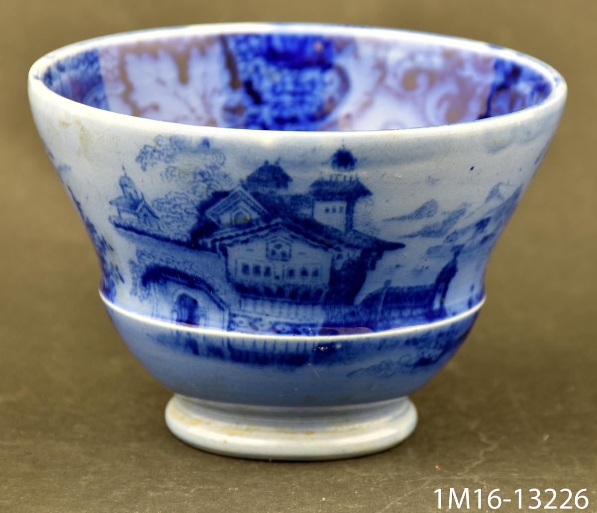 Kopp med flytande blå tryckt dekor med byggnader, landskap och ornamentik med vinranka.