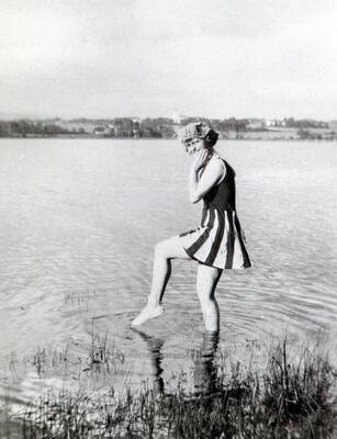 Svart-hvitt foto av ung kvinne iført badedrakt med skjørt, som putter tåa i vannet. (Foto/Photo)