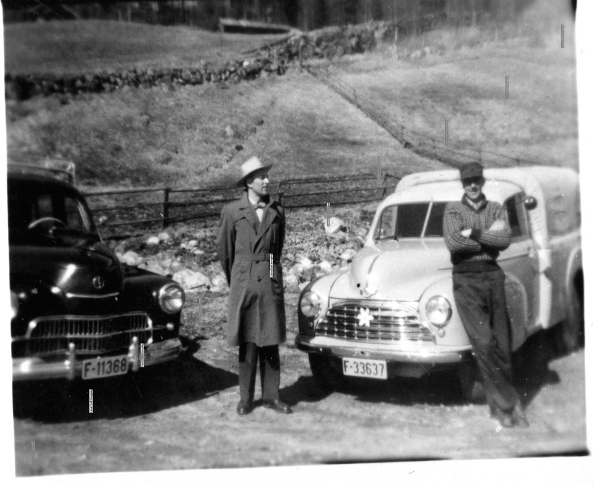 Bilar,frakk,hatt,luve. Til høgre Helge Bakko f.1913 d.1976. Bilen til venstre er ein Wasrsawa. Bilen til høgre er ein Morris varebil, frå fyrste halvdel av 1950-talet.