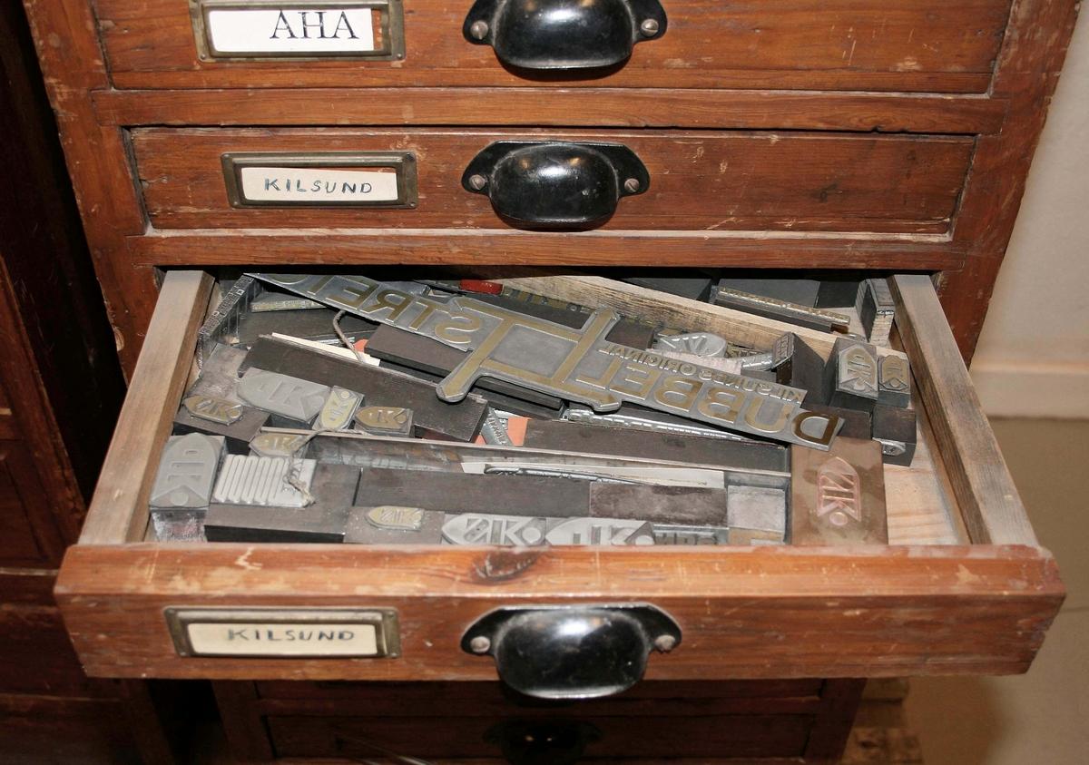Klichéskåp i brunbetsat trä. Fyrsidigt, smalt, med plats för 12 lådor. Varje låda, märkt med olika företagsnamn med en pappers-etikett. På insidan, förvaras olika klichéer, som användes för tryckning, för respektive företag. 3 etiketter saknas. Lådorna med svartlackerade draghandtag.  Funktion: Förvaring av klichéer. Användes för tryckning på papper  Familjeföretaget AB J.F. Björsell startades 1888 i Borås av Johan Fredrik Björsell och var verksamt inom kontorsvaru- och tryckeribranschen. Johan Fredrik Björsell efterträddes av sin son Allan Björsell.  1965 övertog Anders och Åke Björsell ledningen av bolaget, som 1997 såldes till ett holländskt företag.