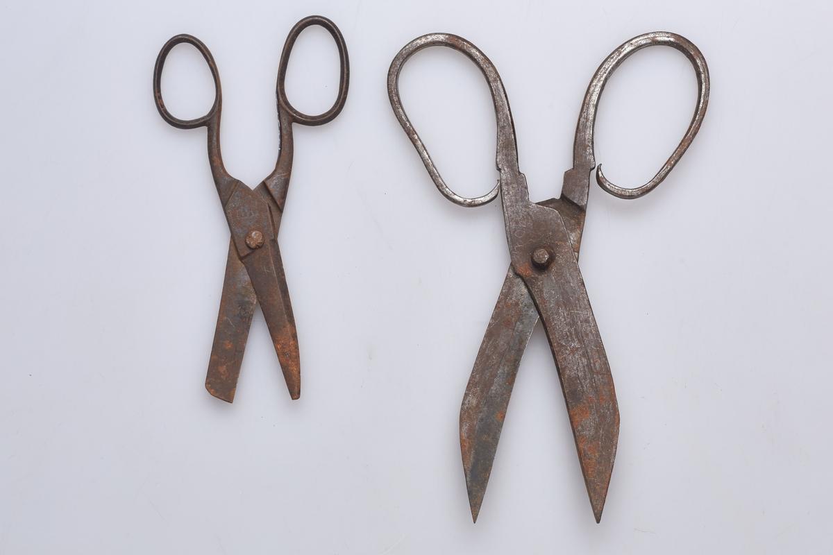 """To sakser i jern. (a) ser ut til å være smidd, mens (b) ser ut til å være støpt. (a) har innstemplet en """"D"""", (b) har innstemplet """"patent""""."""