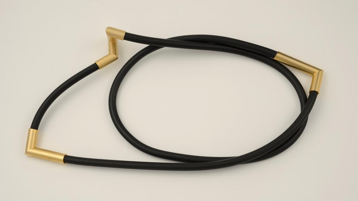 Halssmykke som består av en gummislange og tre påtredde ledd i forgylt messing. To av leddene har L-form, det tredje er formet som to sammenstilte L-former.