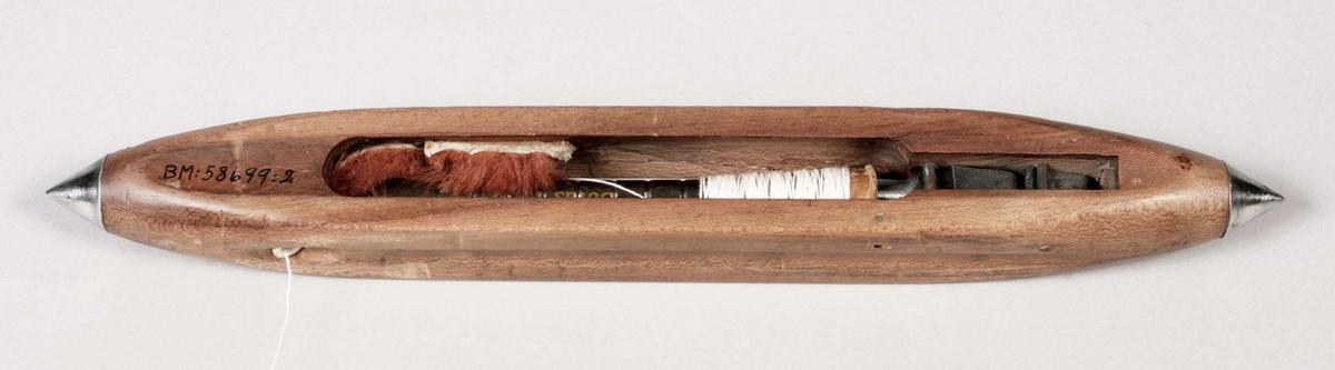 Avlång skyttel av trä med metallspetsar. Spindel av metall. Manuell trådning. Proveniens Halla Textil AB, Överlida.