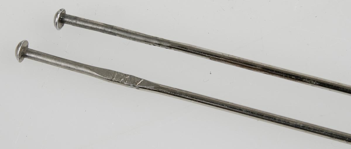 Ett par stickor av metall, under knoppen en utbuktning med text: AXT på ena sidan och siffran 2 på andra sidan.