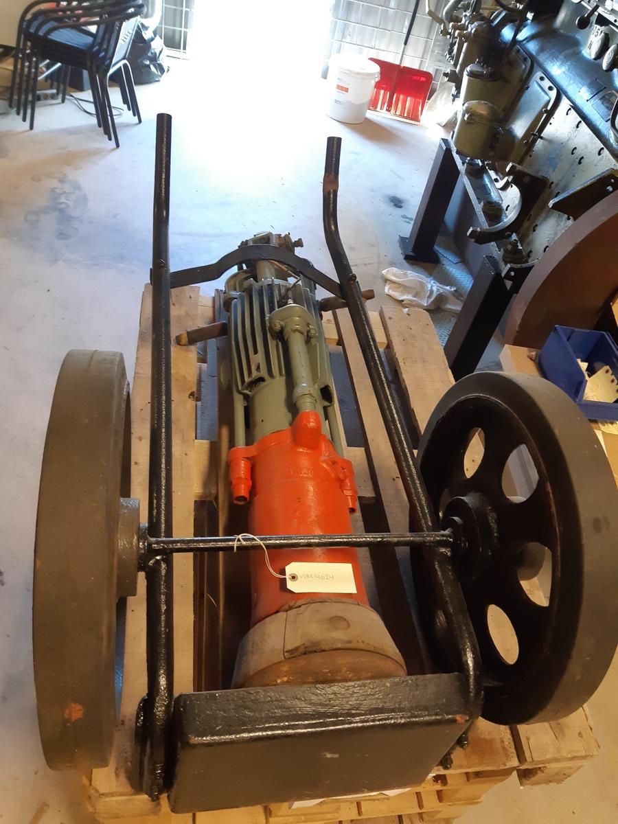 """Motordriven jordstöt, kallas även """"Hoppjerka"""". I toppen bensinmotor. Gummihandtag. Rödmålad nederdel, gråmålad överdel. Nederdelen träbekädd. Skylt: """"AB Vibro-verken, Stockholm, nr 49530, typ MJP"""". Mässingsskylt på jordstöten: """"Vägförvaltningen i P län, maskinnr JS 1"""". På dragkärra av järn med massiva gummihjul."""