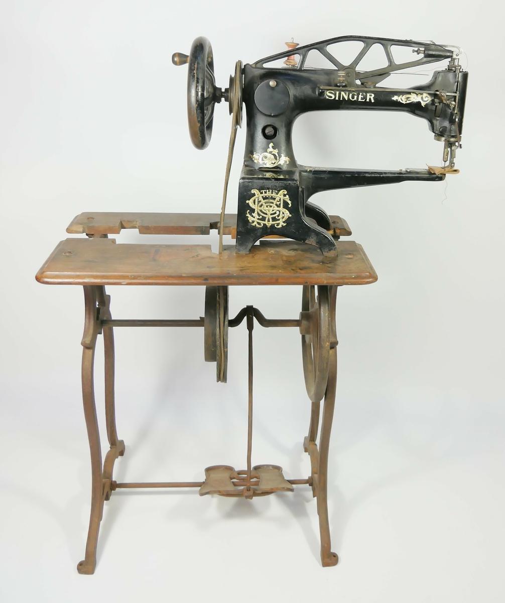 Svart symaskin med gullfarget dekor. Symaskinen er festet på ett bord med pedal, til pedalene er det festet en jernstang med ett hjul med en reim. Reimen går opp til et hjul på symaskinen. På symaskine er det en rosa snelle med svart tråd, og en brun tekstilbit.    Påskrift:  THE SINGER MANUFACTURING COMPANY // TRADEMARK    Påskrift:  29 K 4   Påskrift:  F3404514