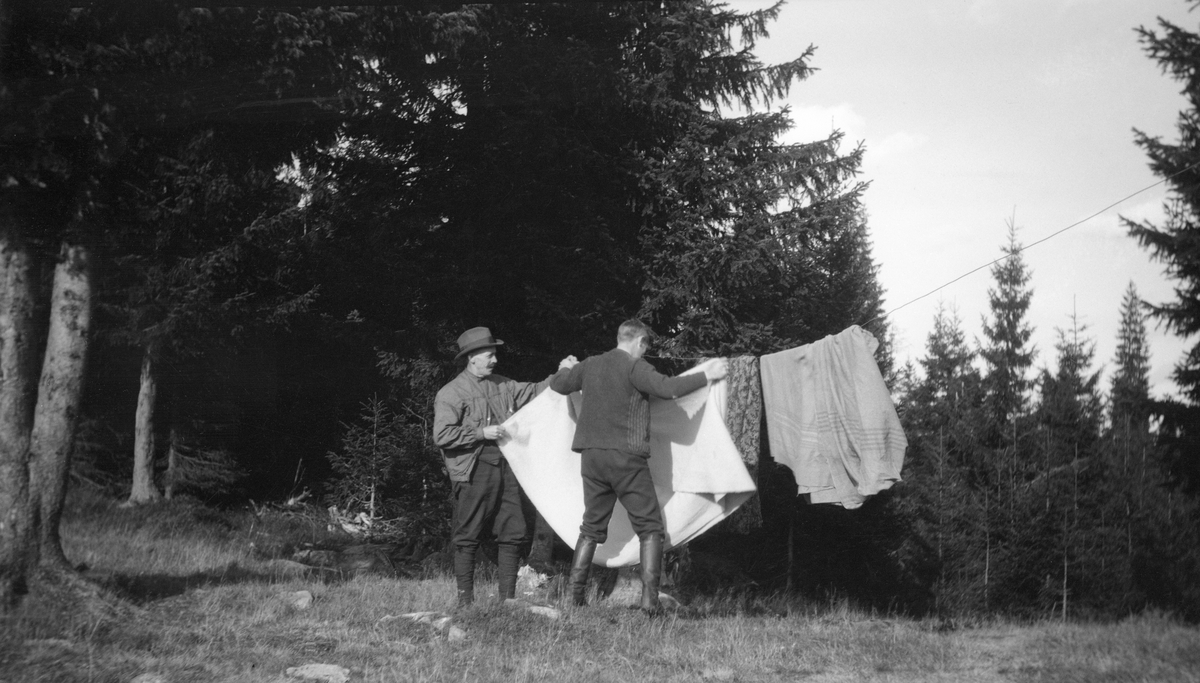 Skog. To personer. Tørking av sengeklær, eller muligens et telt.