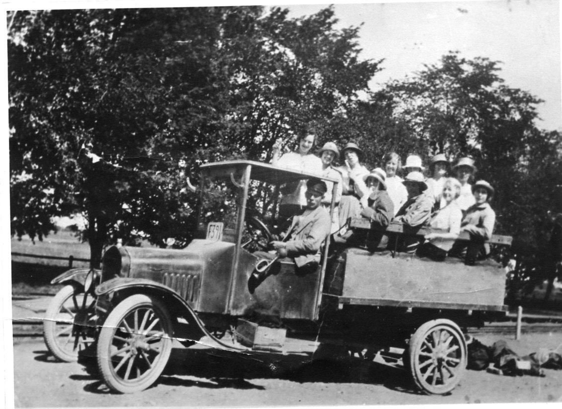 En lastbil med säten på flaket. Vid ratten sitter bilens ägare Valfrid (Gottfrid?) Gustafsson i Uppgränna och på flaket sitter elever vid Kortebo bibelinstitut som är på utflykt i Gränna. Det är pingstafton 1921. Bilens registreringsnummer är F391.