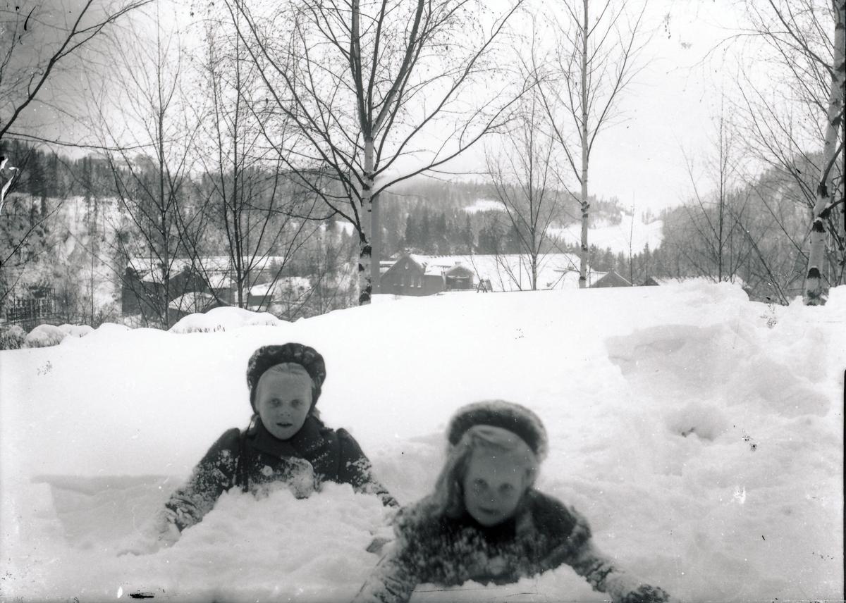 Eia og Lisbeth Rydgren leker i snøen utenfor bestyrervillaen på Kistefos. Industribygninger og skog i bakgrunnen.