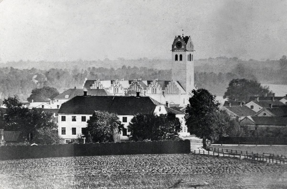 Växjö från nordväst, ca 1880. I förgrunden syns den s.k. von Baumgartenska gården i kvarteret Gripen, byggd i slutet av  1700-talet av kommerserådet Bergius. Till vänster om den skymtar Karolinerhuset och bakom detta syns domkyrkan med  sitt torn.
