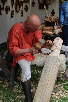 Mann i middelalderklær sitter og skjærer ut et ansikt på en trestokk.. Foto/Photo