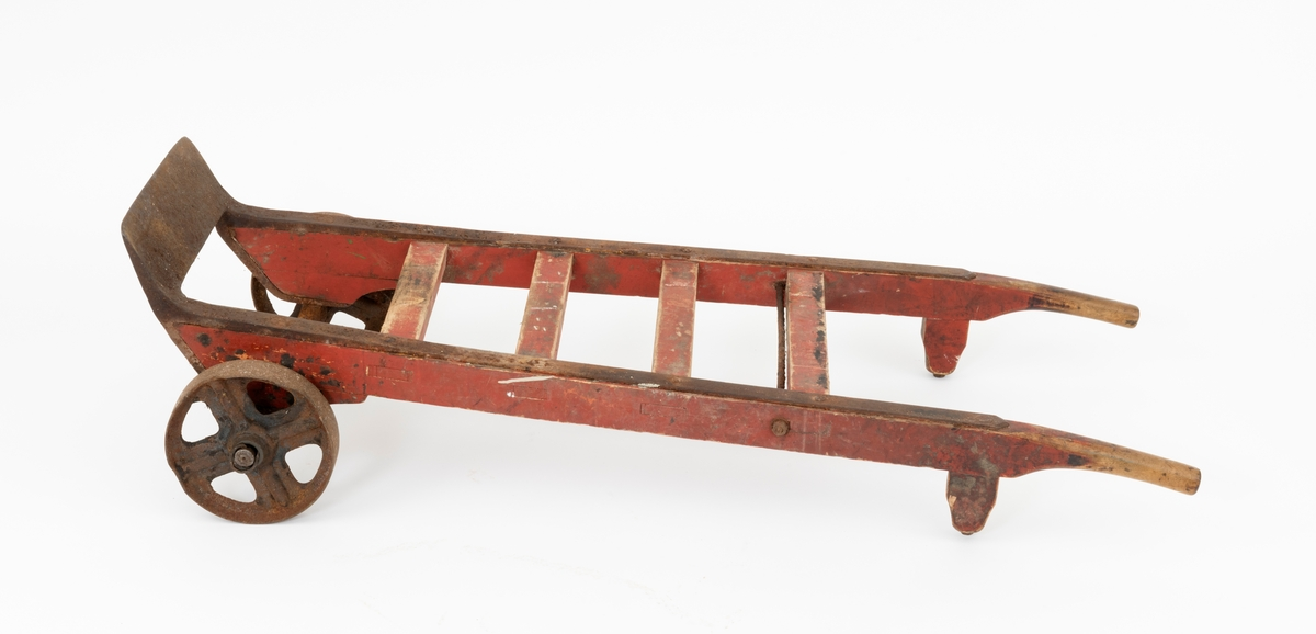 Sekketralle, lagd ved Aadals Brug Jernstøberi og Mekaniske Værksted, en bedrift som ble etablert ved Svartelva i Løten omkring 1840 og var i virksomhet til den ble herjet av brann i 1928. Sekketralla er lagd av jern og tre. Den er bygd på en 57 centimeter lang jernaksling, der den midtre delen har et rektangulært tverrsnitt (2.5 X 3,0 centimeter. I ytterendene av denne akslingen er det om lag 8 centimeter lange sylindriske endeledd med cirka 2,4 centimeters endetapper. På disse er det montert støperjernshjul med drøyt 22 centimeters diameter og 4,8 centimeter bred bane. Den nevnte banen er noe avskallet i ytterkant, særlig på det som sett i brukerens perspektiv er det venstre hjulet. Hjulene har fire grove eiker hver. På den nevnte akslingen er det montert ei treramme med to cirka 134 centimeter lange armer og fire tverrtrær som er inntappet mellom disse armene med en innbyrdes avstand på 13 centimeter. Tappingene er låst ved hjelp av et rundjern med gjengete ender som er tappet gjennom armene tett inntil det øverste tverrtreet og strammen ved hjelp av endemuttere med underliggende jernskiver. I fronten av tralla er det montert et skråstilt 35-36 centimeter bredt jernbrett i forlengelsen av beslagsstenger som beskytter trallearmenes oversider. Også de fremre endene av armenes undersider, der det også er klosser som akslingene er forankret i, er jernbeslåtte. Avstanden mellom trallearmene tiltar noe fra den fremre mot den bakre enden. Her er de gitt et avrundet tverrsnitt, slik at de skulle kjenes gode å holde i. På undersida, like framfor handtakene, er det inntappet 9 centimeter høye treføtter, fastlåst ved hjelp av gjennomgående jernbolter fra jernbeslagene på oversida av armene. Tralla er malt med en rødbrun farge. På undersidene av de to øverste tverrtrærne finner vi tekstene «AADALS BRUG» og «No 2», påført med svart maling ved hjelp av sjablong. På det øverste tverrtreet finner vi også svijernstempelet «HARALD HANSSEN  LØTEN ST.». Harald Hanssen drev kolonialbu