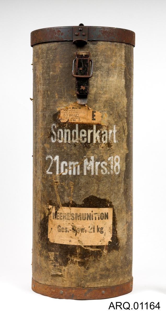 Oppbevaringsboks for ammunisjon til den største ladningen for en 21 cm Morser 18. Boksen er en sylinder og har jernlokk og jernbunn. Selve boksen er laget av meget tykk papp. Jernlokket er hengslet på med nagler inn i pappen og jernbunnen er også naglet inn i pappen. Meget solid. Lokket er foret med tekstil.