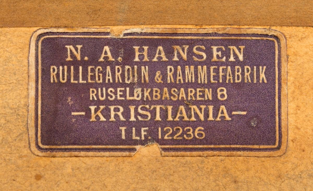 Svart-hvitt-fotografi av Hanestad tjærefabrikk i Øvre Rendalen. Denne virksomheten ble drevet av skogeieren Andreas Mohr Øvergaard på garden Østre Hanestad i Rendalen og kollegaen Otto Aakrann, som bodde på Gårder i Elverum i perioden 1911-1920. Produksjonsanlegget lå på førstnevntes eiendom. Det besto av en bygning som later til å ha vært reist i bordkledd bindingsverk. Midtpartiet hadde to etasjer og bølgeblikktekket saltak. Langs begge langveggene var det enetasjes utbygg med pulttak. Både midtfløyen og den ene sidefløyen hadde innkjøringsporter på den gavlveggen som vendte mot fotografen da dette bildet ble tatt. Sentralt på hovedfløyen var det et skilt med virksomhetens navn. I terrenget til venstre for fabrikken lå det digre hauger med tyrived, råstoff til produksjonen. Foran og på høyre side av bygningen sto det en del trekasser, som muligens også kan ha rommet slik ved. Hovedråstoffet i produksjonen var nemlig tyriholdige furustubber, som måtte brytes opp av bakken og lufttørkes før veden kunne kjøres til fabrikken, noe som antakelig ble gjort på sledeføre vinterstid. SJF.14704 viser samme bygning fra en annen synsvinkel.