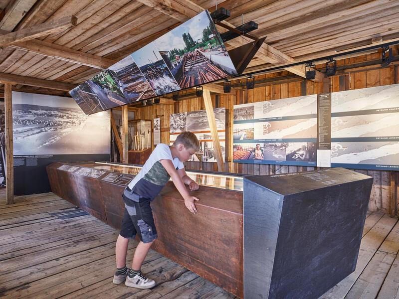Foto fra fløtingsmuseet. Gutt står og ser på modell av fløtingsanlegget på Fetsund. (Foto/Photo)