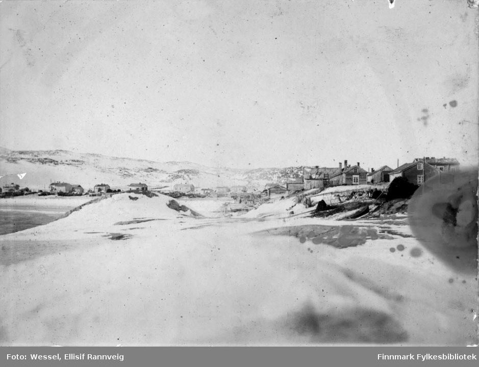 Bugøynes i 1898. Bildet er tatt ved fjæra og oppover mot bebyggelsen. Bildet er svært bleket midt på bildet, men detaljene er gode på sidene av bildet.