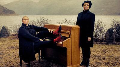 Inger Kristine Riber og Reidun Horvei poserer ved utendørs piano ved fjorden. Foto/Photo