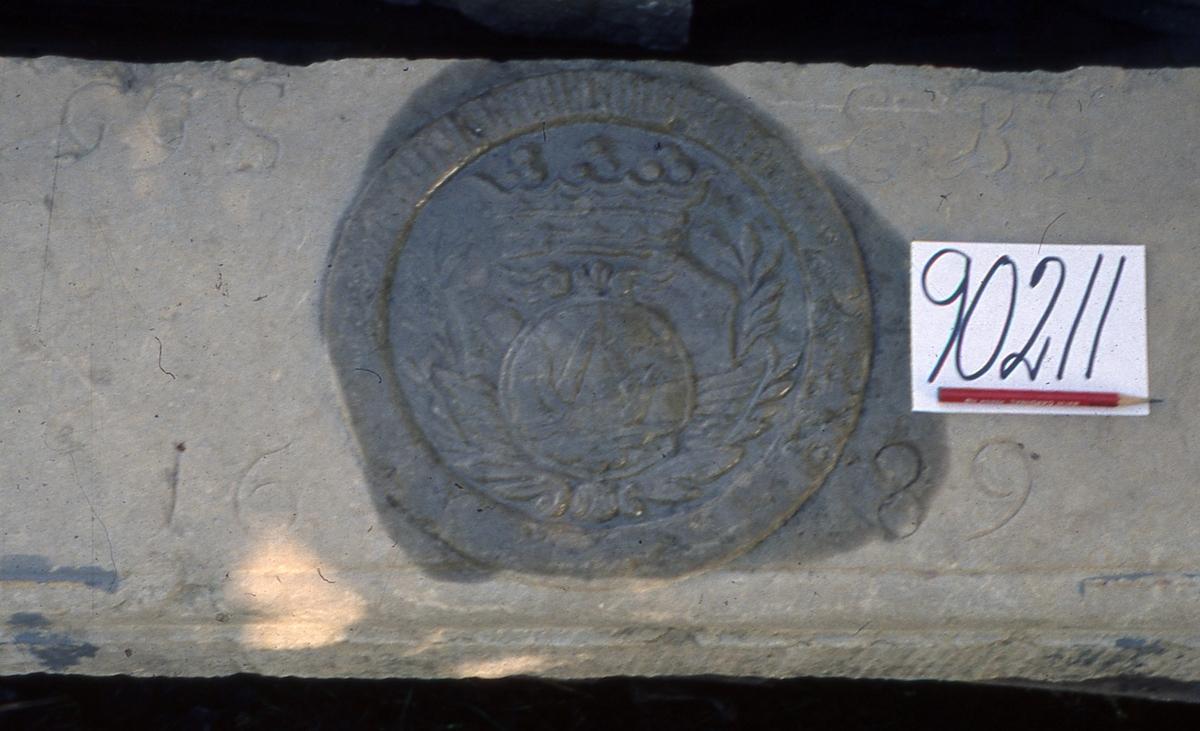 Planslipad, rektangulär vapentavla med Oxenstiernas vapen i mitten. Detta består främst av en oxpanna. Under denna finns monogrammen GGS, EBS och årtalet 1689.  Vapentavlan tillvaratogs av givaren i samband med rivningen av Stora Hov 1957. Tavlan var då placerad i hallen ovanför en dörr. Stora Hov har tidigare varit i släkten Oxenstiernas ägo.