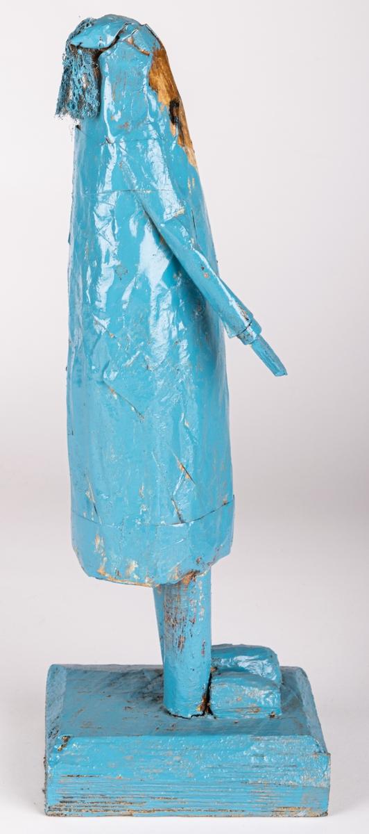 Skulptur av trä och papper. Figur/människofigur, helt blåmålad. Ansikte i beige med detaljer i svart. Mössliknande form på huvudet, med garntofs bak.