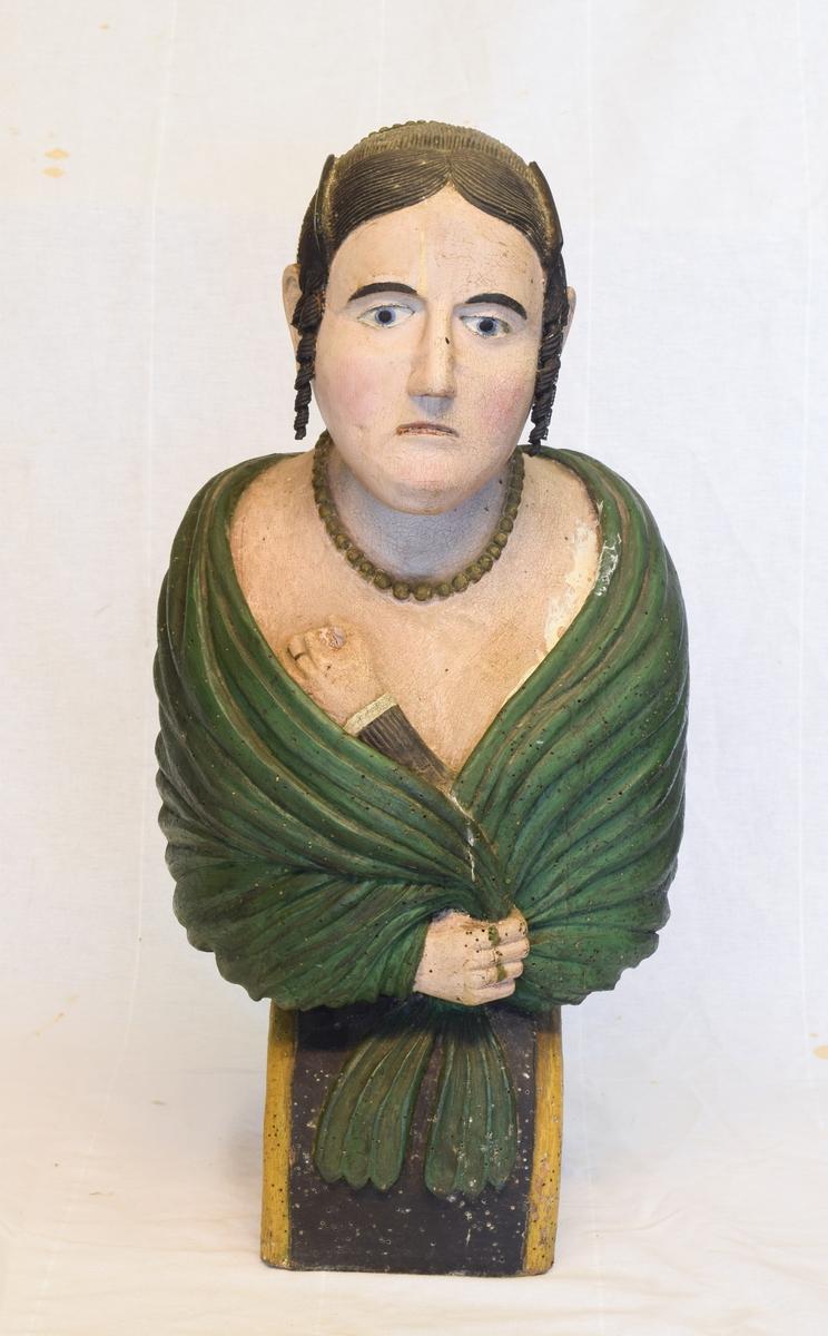 Portrettbyste av kvinnehode. Skulle brukes som gallionsfigurer men kan og ha vært brukt som dekorasjon i et hus. Sortmalt hår med hengekrøller ved ørene og grønt sjal.