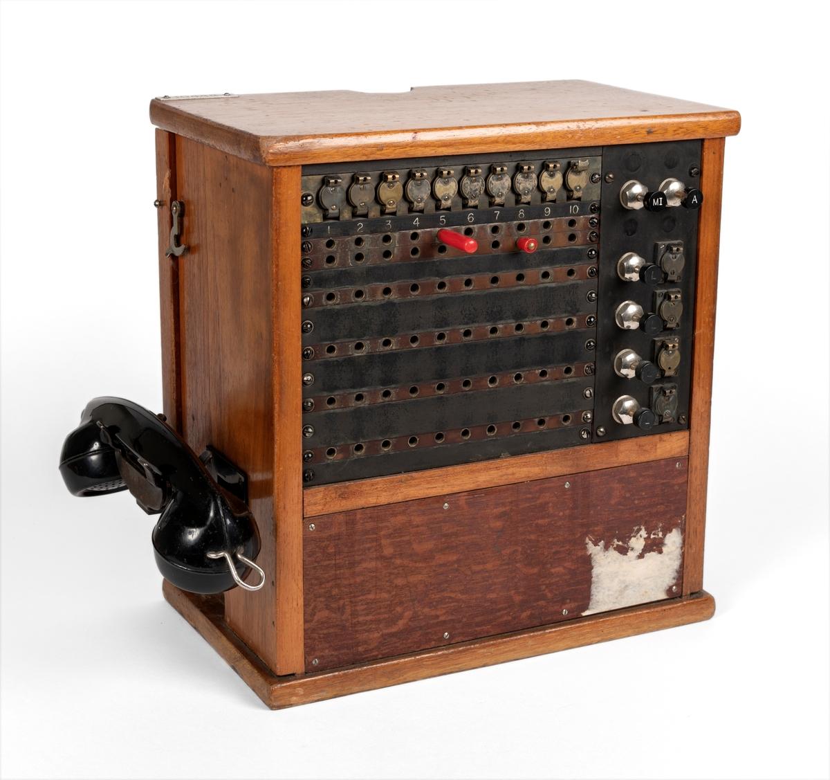 Trekasse med oppheng for telefonrør på venstre side. På forsiden hull for oppkopling til ulike nummer.
