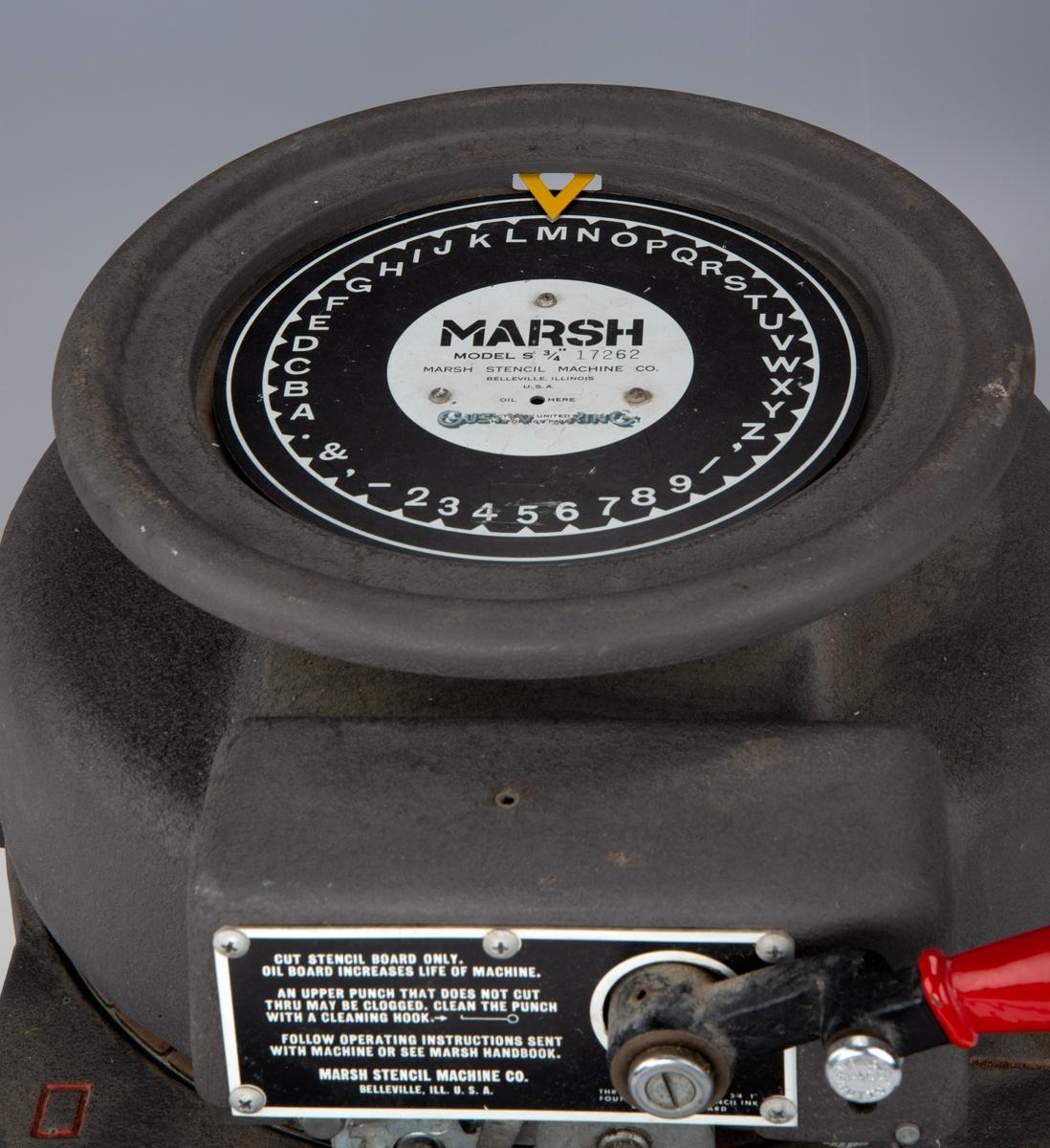 Grå maskin med detaljer i rødt. En sirkulær del på toppen kan snurres rundt for å velge bokstav som skal trykkes ut.
