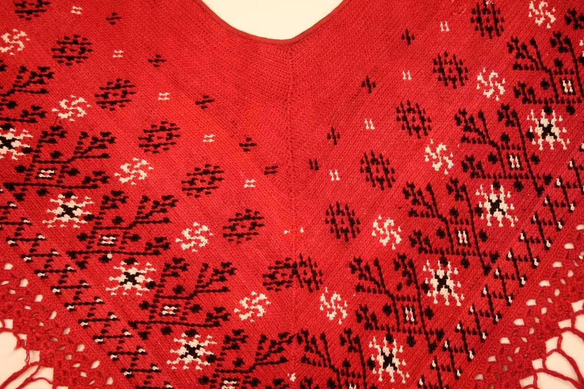 Schal, hjärtvärmare. Till Nås kvinnliga sockendräkt. Virkad, fastmaskvirkad av rött ullgarn, mönster av svart ullgarn och vitt bomullsgarn. Spetsvirkad kant i stolpae med iknuten frans. På halssidan kantad med rött ylleband. Bäres i kors över bröstet. Rött och svart ullgarn i Z-tvinning, vitt bomullsgarn i S-tvinning.