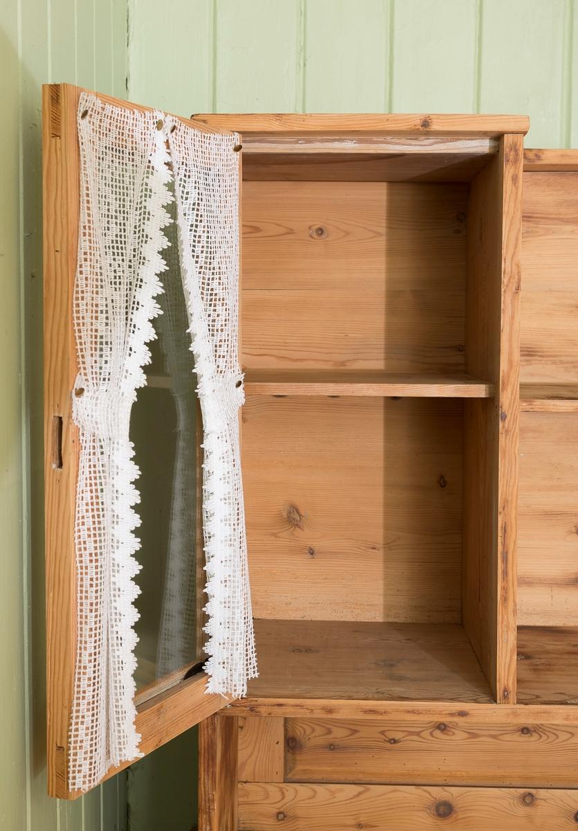 Skap med to skuffer og løs overskap. Overskapet har to glassdører med heklet pyntegardiner. Mangler lås på begge glassdør og den ene skapdøra. Har hatt flere lag med maling og/eller lakk, som har blitt pusset.
